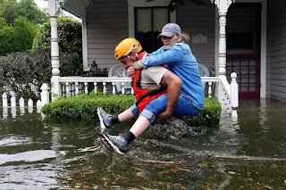 A Texas National Guardsman carries a resident from her flooded home following Hurricane Harvey on August 27, 2017, in Houston, Texas. (Credit: Lt. Zachary West/Army National Guard via Getty Images) Click to Enlarge.