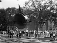 A photograph of a crowd watching a large bell being hoisted up.