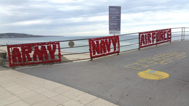 "At the start of the Brighton jetty, on the left hand railings are three transparent mesh banners spelling out words made by crocheted and knitted poppies: ""Army"", ""Navy"" and ""Air force"" in capital letters. there is a yellow hopscotch court painted on the jetty pavement in front of the banners. Beyond the jetty is Brighton beach with further views to Marino, Hallett Cove and Port Stanvac. The water of St Vincents Gulf is calm with an overcast sky."