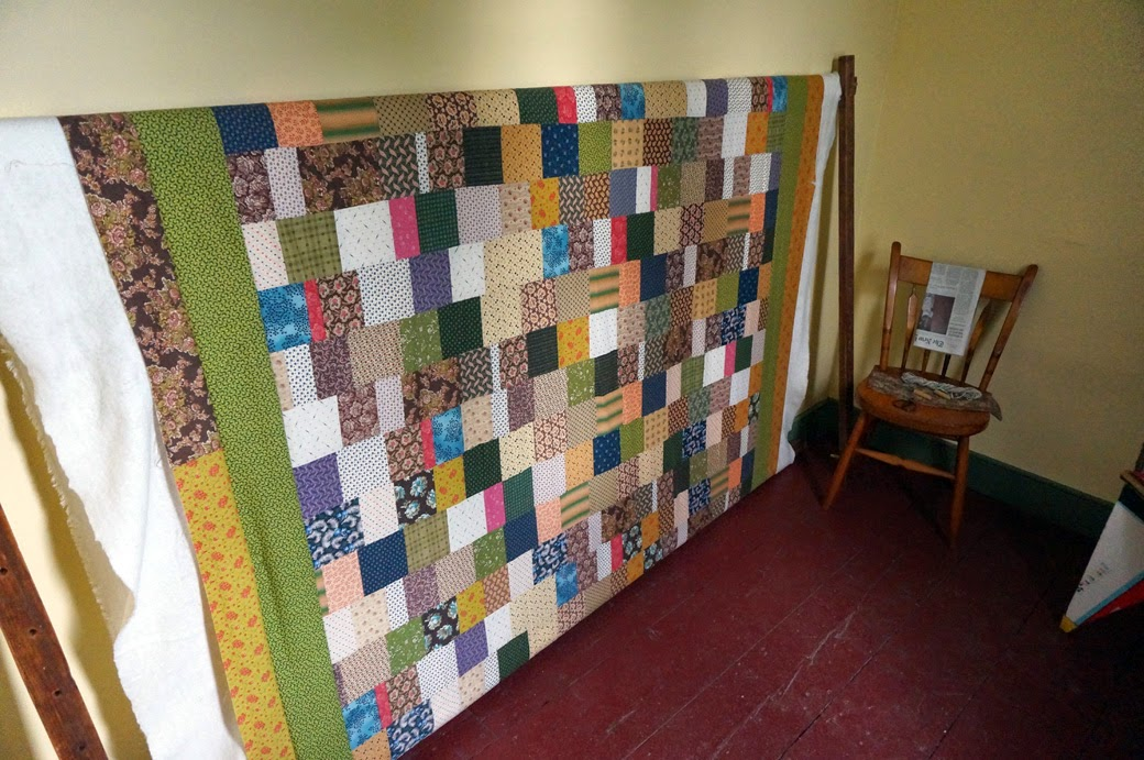 Interior of Hunterfly Road House with chair next to quilt on quilt rack