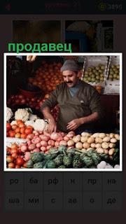 за прилавком стоит продавец и продает овощи и фруты