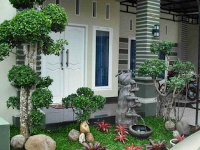Desain Taman Depan Rumah Bergaya Minimalis Modern Dengan Tanaman Akar Tinggi dan Kolam Air Terjun Mini Yang Dihiasi Bebatuan dari Alam