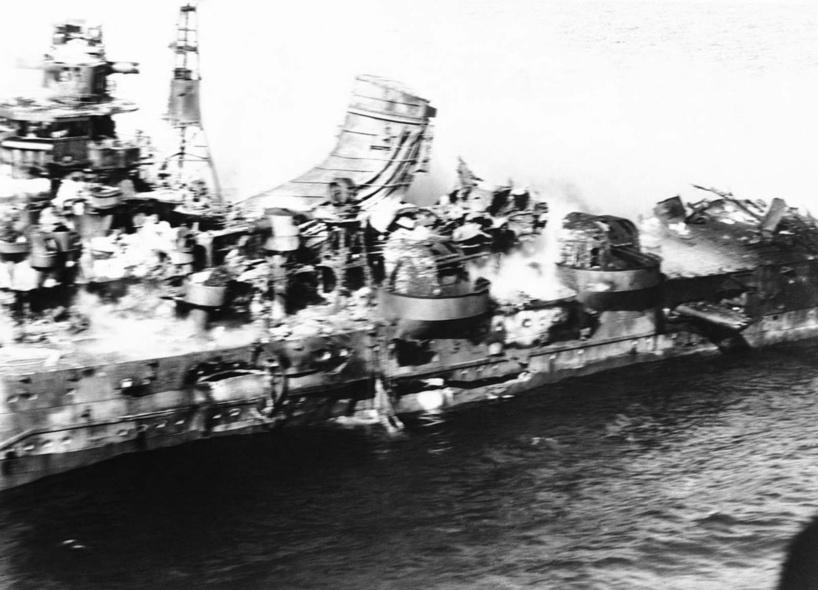Flying dangerously close, a U.S. Navy photographer got this spectacular aerial view of a heavy Japanese cruiser of the Mogima class, demolished by Navy bombs, in the battle of Midway, in June of 1942. Armor plate, steel decks and superstructure are a tumbled mass.