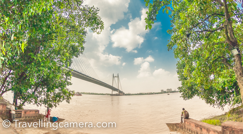 While travelling, I decide my own itinerary or follow the experts in the field or blogging or sensible media. The Beacon team was very helpful in exploring Kolkata in best way. Sohail suggested to go for early morning walk around Princep Ghat and this was one of the best experiences of Kolkata.I left from my hotel in Elgin and planned to take local bus to reach Babu Ghat. Buses were relatively empty in the morning and it was an interesting experience. This was going to Howrah from Elgin and was always on the move. It was hardly stopping to pick passengers. Driver used to press break for few seconds and then start when passenger is on board. This bus journey costed me 8 rs.I got down at Babu ghat. When you are facing Ganges at Babu Ghat, you see Howrah Bridge on the right and Vidyasagar Setu on the left. I headed towards Left and Princep ghat is on the same side.Above is the photograph of Princep ghat, which was relatively quiet as compared to other ghats I crossed. Babu Ghat and Pani Ghat had lot of pilgrims taking holy bath. Vidyasagar Setu is very close to the Princep Ghat.There is a nice walking area from Babu Ghat to Princep Ghat, through green landscapes and well paved path around the ghats. The whole stretch is well maintained and clean, although some of the views to Ganga were disappointing. I will be sharing more about that in a separate post soon, but overall this walk is very enjoyable and full of experiences.There is a railway track passing by this pathway and few local trains cross through this track. There is a railway station at Princep Ghat and I saw lot of folks waiting for the train there. I spent around 2 hours around these ghats and 2 trains crossed through this railway track.At almost every 150-200 meters you can see these beautiful boats parked around the ghats. They were gearing up for the day and few of the folks had already arrived who wanted to take a ride on ganges.Above is a photograph from Pani Ghat which comes on the way from Babu Ghat t