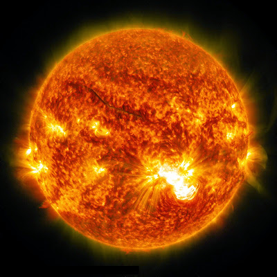Full disk image in orange color tones of the sun showing a massive X3.1 solar flare