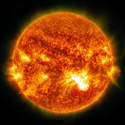 Full disk image in orange color tones of the sun showing a massive X3.1 solar flare