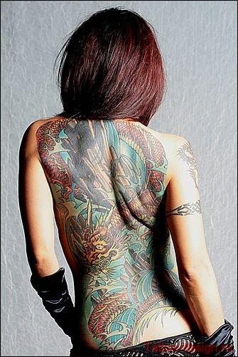 vemos a una mujer posando luce el tatuaje de un dragon