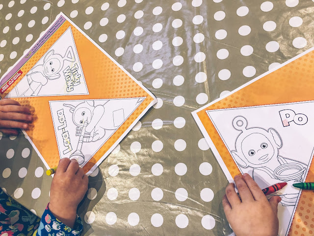 Two toddlers colouring in Teletubbies bunting available from the Tubby Playdate Pack