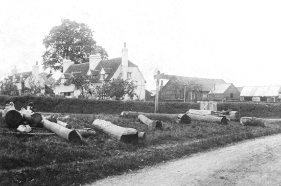 Photograph of Nash's Corner with wood drying for use by Nash. Oak Cottage stands where the oak tree was 1900s. Image from Ron Kingdon