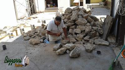 Bizzarri acertando a pedra para fazer um murinho de pedra com pedra moledo com as escadas de pedra, os caminhos de pedra em construção com pedra em São Paulo-SP.23 de setembro de 2016.