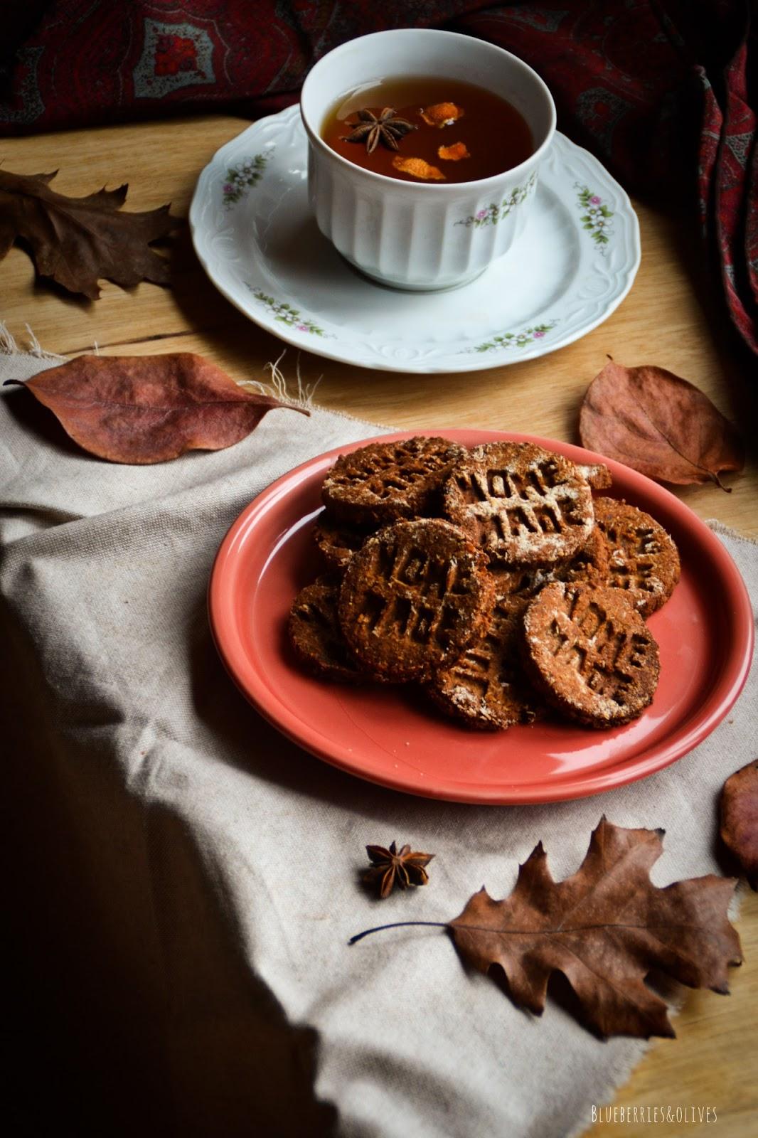 Servilleta vintaje burdeos, taza porcelana antigua con té, Galletas caseras sobre plato cerámica rojo, fondo madera oscuro, manzanas rojas, hojas secas otoño, paño de lino beige