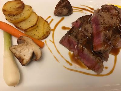 4 potetskiver, en gulrot, halv sopp og vårløk til venstre. Oppskårne kjøttbiter og sirkler med saus til høyre.