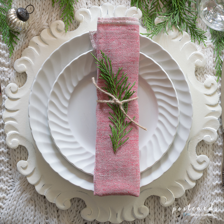 Christmas place setting with white dished and washed red linen napkins