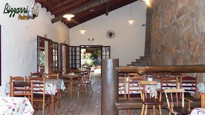 Detalhe da parte interna com as mesas e as cadeiras de madeira, a parede de pedra, o piso de tijolo de demolição com a parede pintada de branco e os caixilhos de madeira.