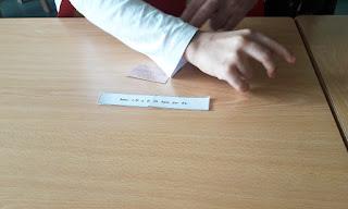 Mão de um aluno a completar um provérbio