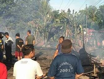 Warga menyaksikan sisa-sisa panglong di Labuhanbatu yang terbakar.