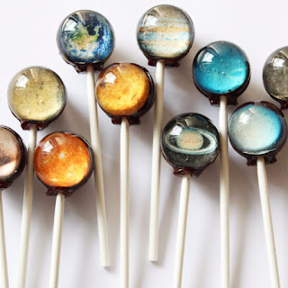 photograph of lollipops with planet images within