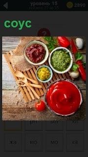 На столе приготовлены  различные соусы с приборами для приема пищи