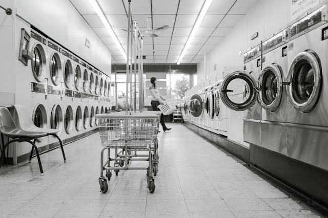a black and white photo of a gal alone in a laundry mat