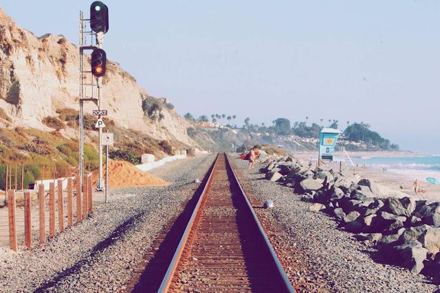 Vía de un tren al lado de una playa