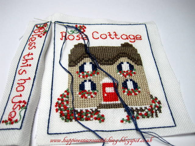 Stitching the border of this pretty cross stitched cottage showing how to make a mattress pincushion