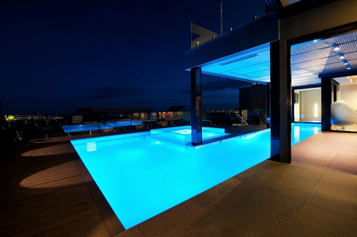 Swimming pool at night in Dream home in black and blue