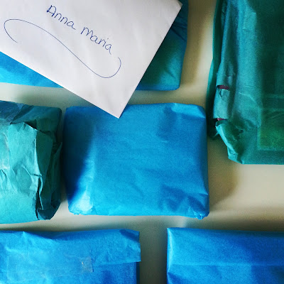 Selection of items wrapped in blue and teal tissue paper, laid out on a tabletop with an envelope on top addressed to Anna-Maria
