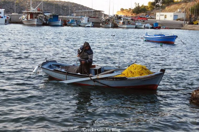 kobieta zwija linę  żółta sieć na spodzie łódki rybaczka port limenas