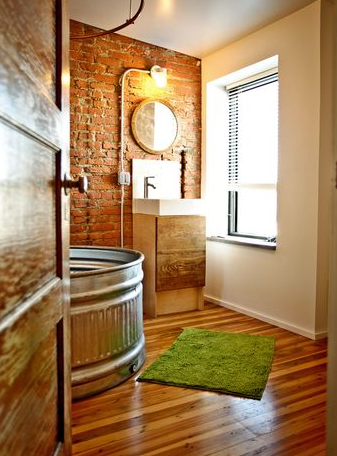 Stock tank tubs is combined with parquet floors and brick walls.