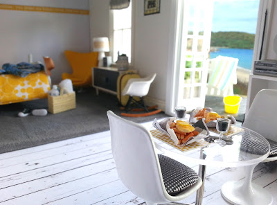 One-twelfth scale modern miniature motel room in white, grey and yellow overlooking the beach through open french doors.
