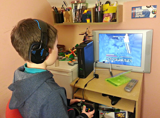 Boy wearing headset, playing game on Xbox 360