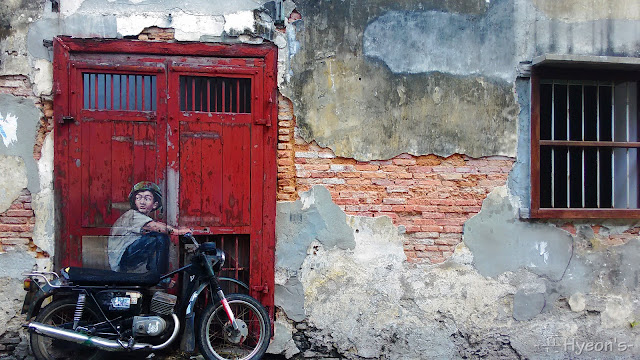 boy on a bike street art penang