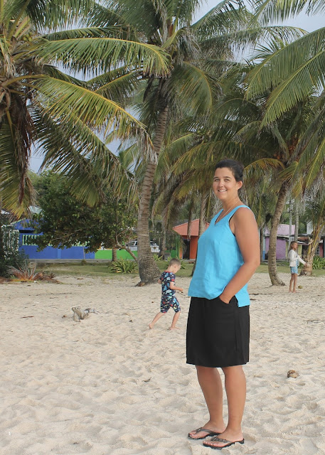 Woman standing on a sandy beach in front of palm trees, wearing a turquoise linen tank top hacked from the free Colette Sorbetto sewing pattern.