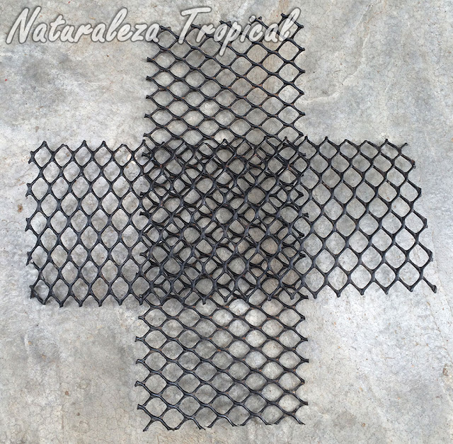 1- Lo primero que debemos hacer es colocar un trozo de rejilla plástica sobre la otra formando una cruz, el centro de la cruz será la base de la maceta.