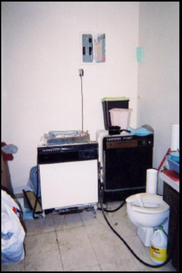 A cluttered room with a portable dishwasher, toilet, trash bags, and unidentified objects on the vanity
