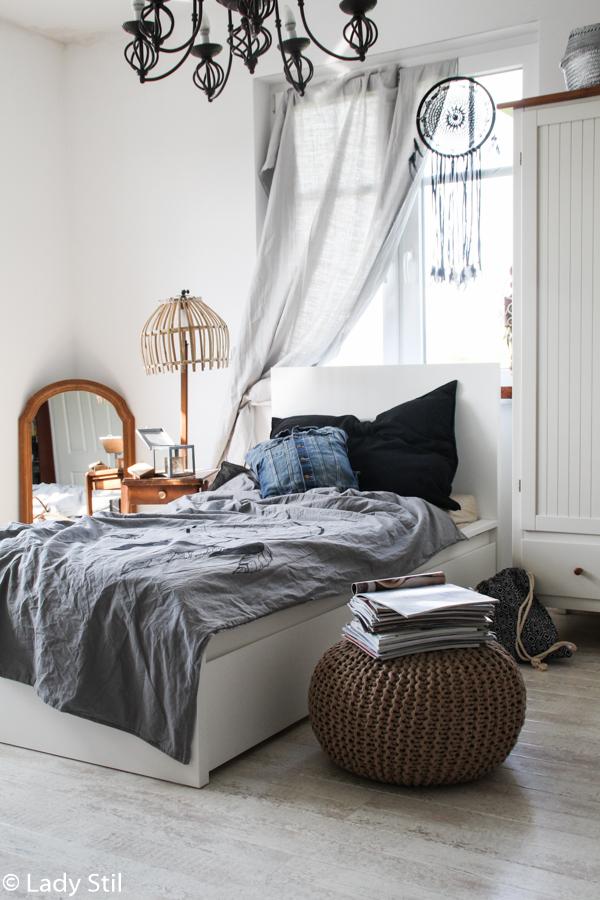 Schlafzimmer mit weißen Möbeln und grauer Bettwäsche mit Traumfänger Motiv sowie Holzspiegel im Boho Look