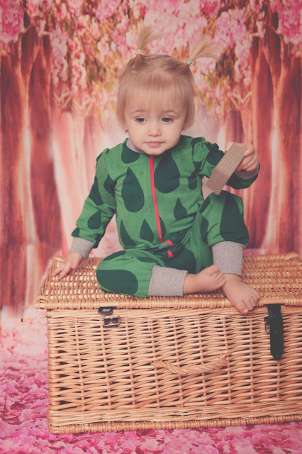 toddler girl wearing green zip up jump suit  with rain drops from me&i clothing