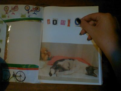 Carátula diseñada con recortes de revistas. Mano de mujer pegando letras recortadas a modo de título, y la imagen de una revista pegada sobre la hoja, muestra la figura de un gato durmiendo