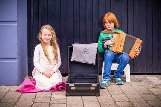 Niños. Niño tocando el acordeón. Niña posando de rodillas