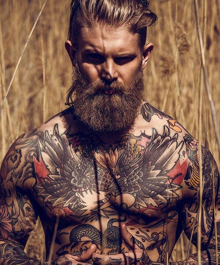 hombre barbudo mirándonos fijamente lleva tatuaje de águila tradicional en las pectorales