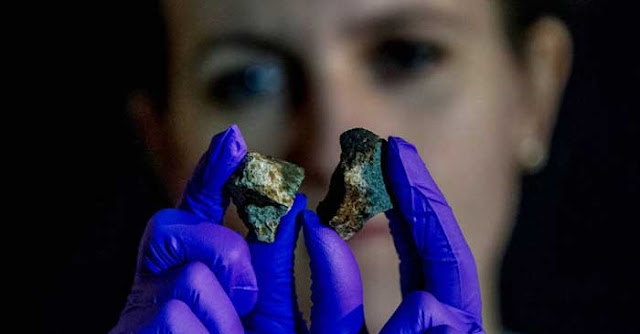 LLNL researcher Megan Bruck Syal examines a pair of meteorites destined to be vaporized by high-powered lasers. Photo by Julie Russell/LLNL.