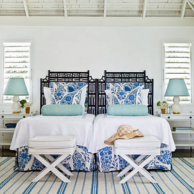 Blue and white bedroom with black faux bamboo headboards, white x-benches and a blue and white striped rug