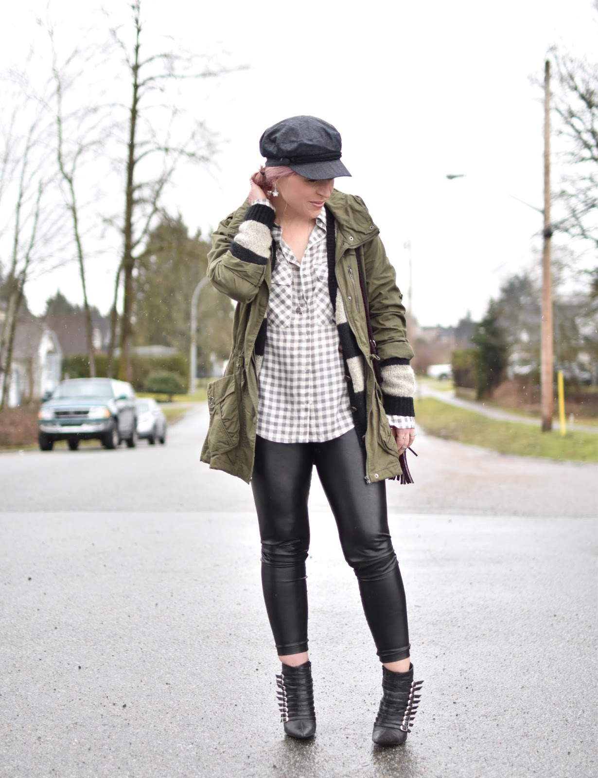 Monika Faulkner outfit inspiration - styling a baker boy cap with a gingham shirt, striped cardigan, army-style parka, and vegan leather leggings