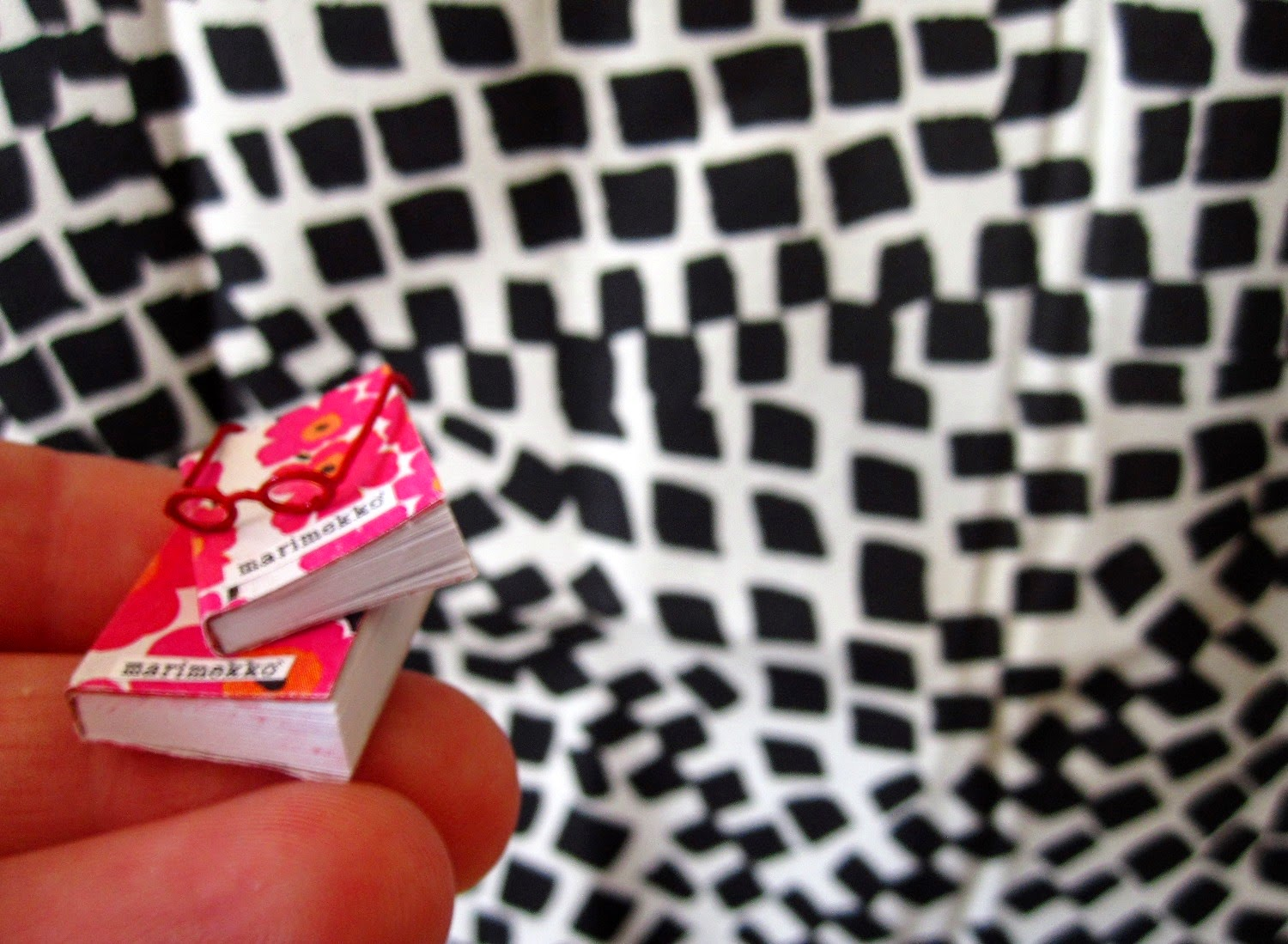 Two miniature Marimekko books and a pair of miniature red reading glasses balanced on fingertips.