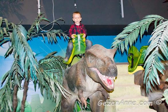 bir dinozorun sırtında eğlenen oğlum, Jurassic Land