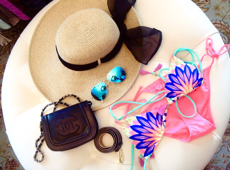 Accessories laid out on a white ottoman. Straw hat with black bow, blue mirrored sunglasses, black crossbody bag with chain strap, pink and navy palm print bikini and black belt with gold buckel.
