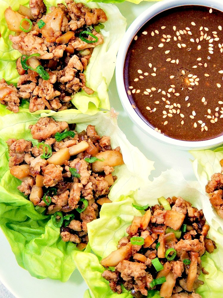 Close up of Copycat PF Chang's Chicken Lettuce Wraps on a white serving platter with dipping sauce in a white bowl.