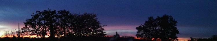 The dark blue evening skyline I see standing on my balcony