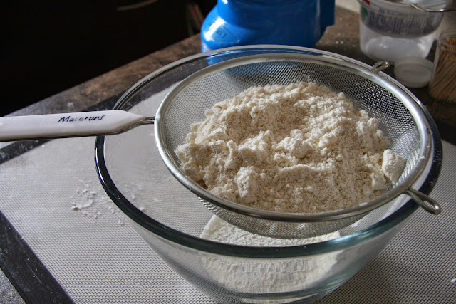 Sifting processed almond meal and powdered sugar.