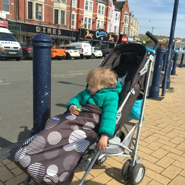 toddler in buggy with coat on by road and shops